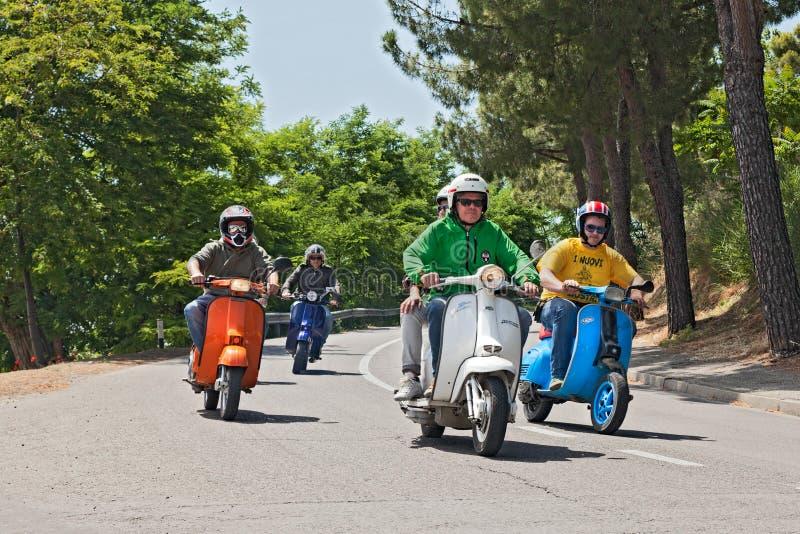Grupo de motociclistas que montam 'trotinette's de um italiano do vintage fotos de stock