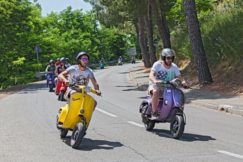 Grupo de motociclistas que montam 'trotinette's de um italiano do vintage foto de stock royalty free