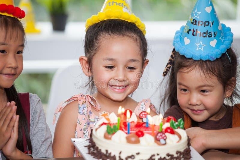 grupo de muchacha feliz de los niños con las velas que soplan del sombrero en la torta de cumpleaños junto que celebra en partido imágenes de archivo libres de regalías