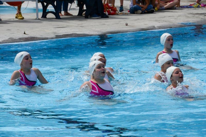 Grupo de muchachas en una piscina que practica la natación sincronizada imagenes de archivo