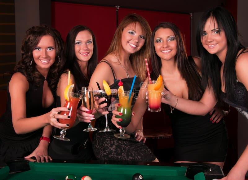 Grupo de muchachas felices que beben los cocteles imagenes de archivo
