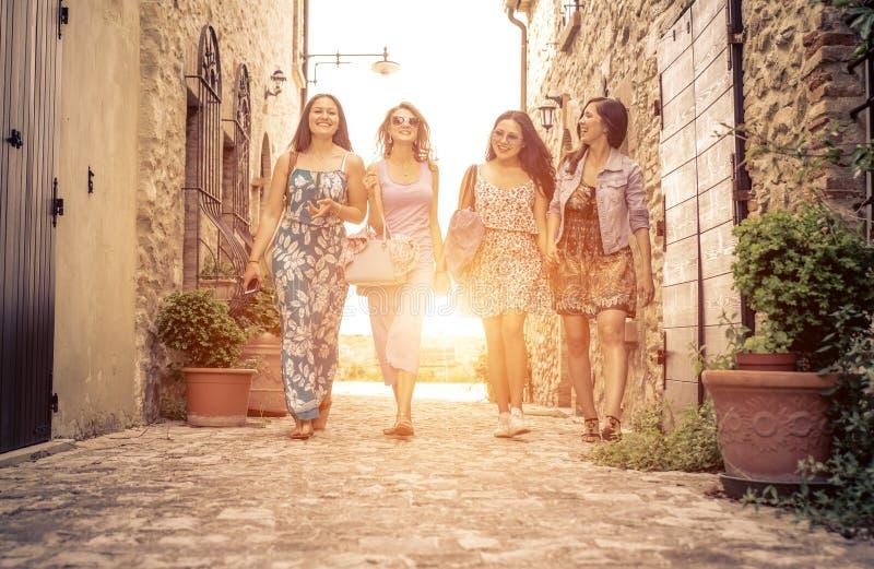 Grupo de muchachas que caminan en un centro histórico en Italia imagen de archivo