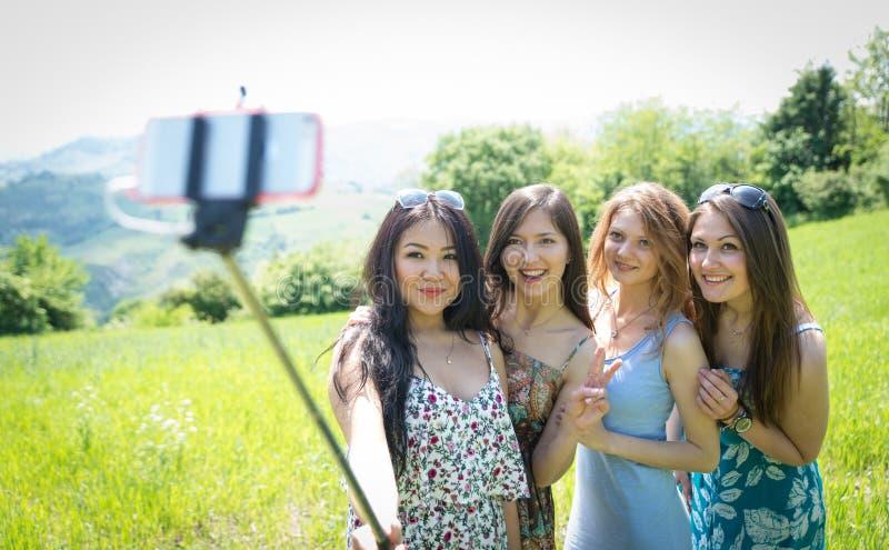 Grupo de muchachas que hacen el selfie con el palillo del selfie fotografía de archivo