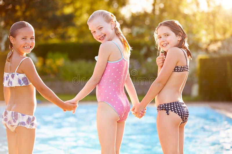 Grupo de muchachas que juegan en piscina al aire libre fotos de archivo
