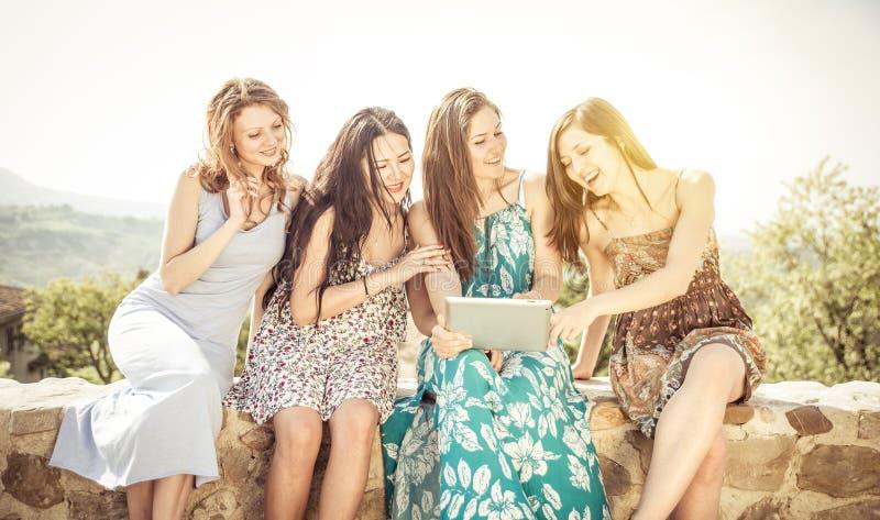 Grupo de muchachas que miran la tableta al aire libre imagenes de archivo