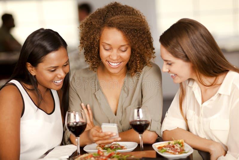 Grupo de muchachas que miran un smartphone fotos de archivo