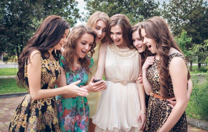 Grupo de muchachas que miran un teléfono celular imágenes de archivo libres de regalías