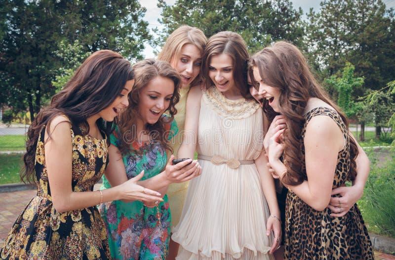 Grupo de muchachas que miran un teléfono celular foto de archivo