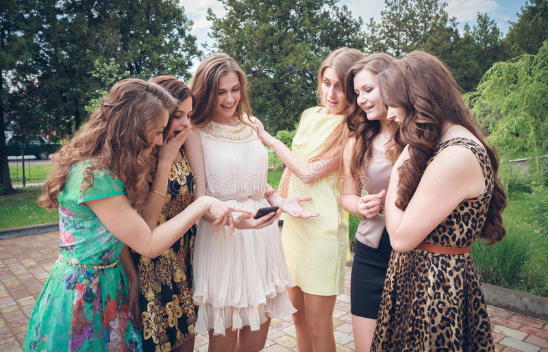 Grupo de muchachas que miran un teléfono celular imagenes de archivo