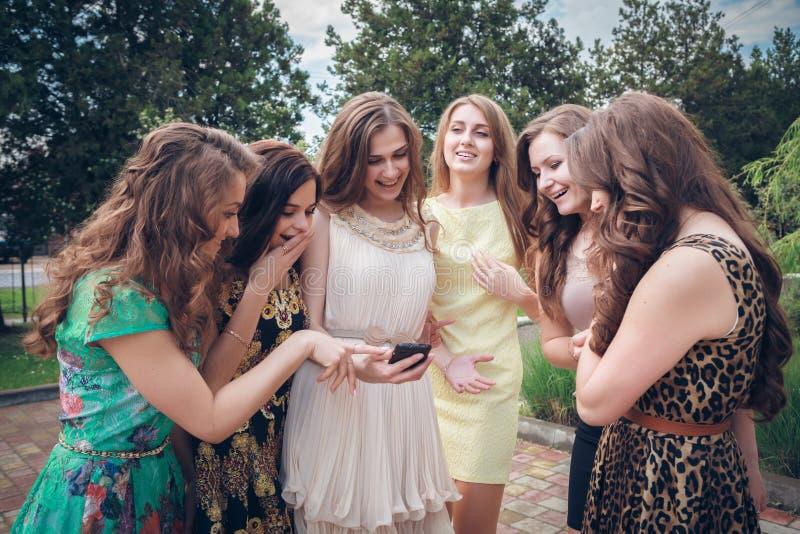 Grupo de muchachas que miran un teléfono celular fotos de archivo libres de regalías