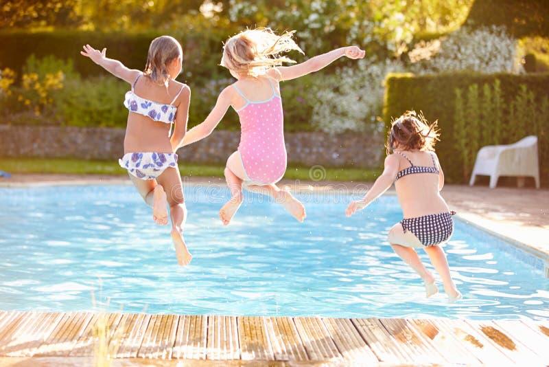 Grupo de muchachas que saltan en piscina al aire libre foto de archivo