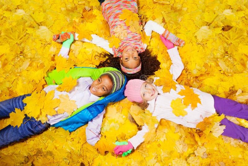 Grupo de muchacho y de muchachas en las hojas de arce imágenes de archivo libres de regalías