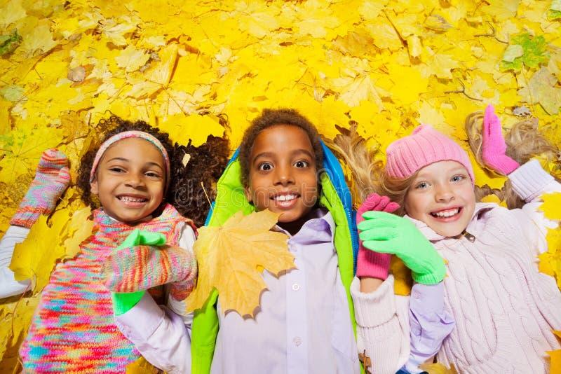 Grupo de muchacho y de muchachas en las hojas de otoño foto de archivo