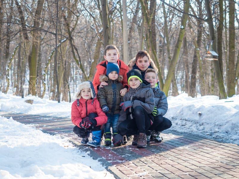 Grupo de muchachos lindos que presentan para la cámara en parque del invierno imagenes de archivo