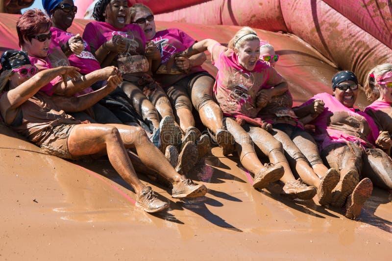 Grupo de Muddy Women Hold Hands Sliding en hoyo del fango fotos de archivo libres de regalías