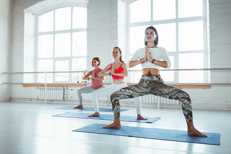 Grupo de mujeres adultas que hacen ejercicios de la yoga juntos en clase de la aptitud La gente activa practica actitudes de la y fotografía de archivo