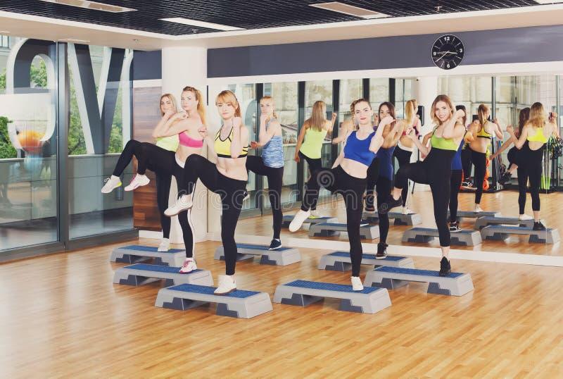 Grupo de mujeres, aeróbicos del paso en club de fitness fotos de archivo libres de regalías