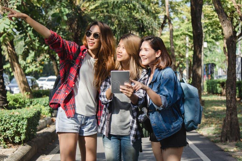 Grupo de mujeres asiáticas que usan la cámara para hacer la foto mientras que viaja en el parque en ciudad urbana en Bangkok, Tai imagen de archivo libre de regalías