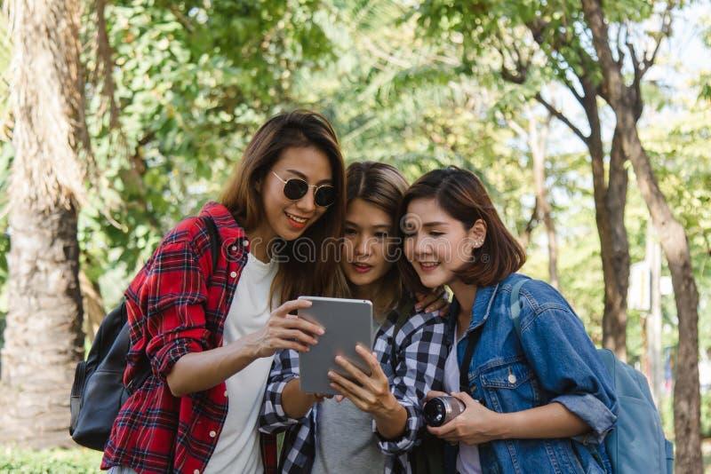 Grupo de mujeres asiáticas que usan la cámara para hacer la foto mientras que viaja en el parque en ciudad urbana en Bangkok, Tai fotos de archivo