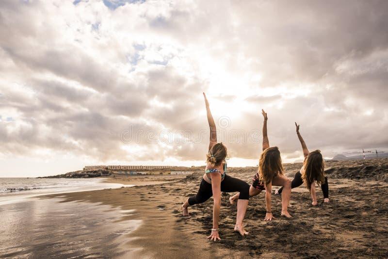 Grupo de mujeres cauc?sicas hermosas jovenes que hacen ejercicios de la aptitud en la playa en la orilla oc?ano y cielo azules en fotos de archivo libres de regalías