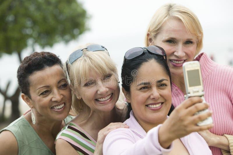 Grupo de mujeres de mediana edad que se fotografían con un teléfono móvil imagenes de archivo