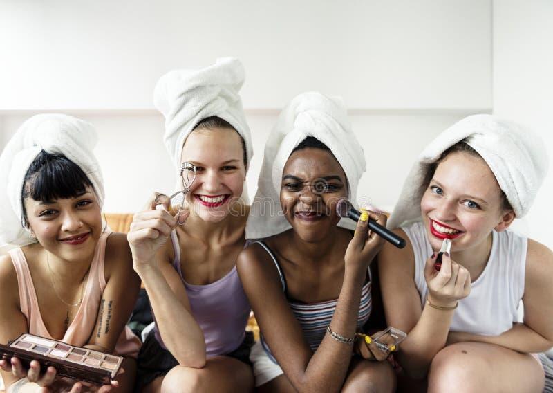 Grupo de mujeres diversas con los cosméticos del maquillaje imagen de archivo