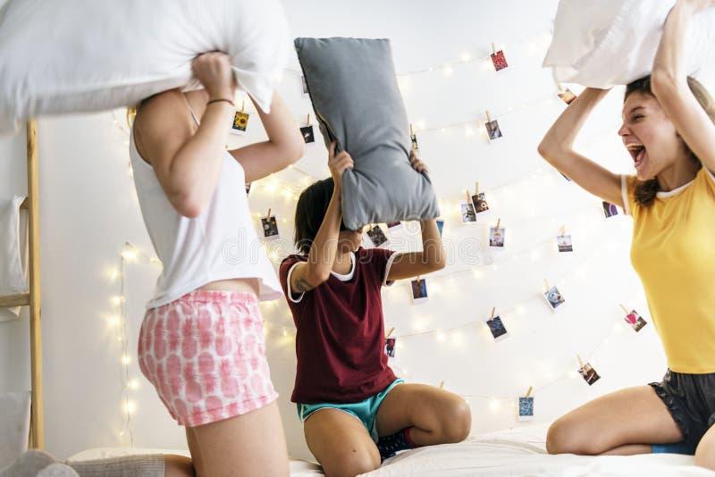 Grupo de mujeres diversas que juegan lucha de almohadas en cama junto foto de archivo libre de regalías