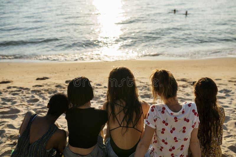 Grupo de mujeres diversas que se sientan en la playa junto imagen de archivo libre de regalías
