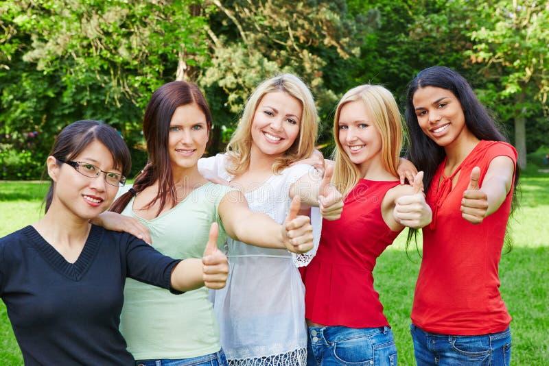 Grupo de mujeres en la naturaleza que detiene los pulgares fotos de archivo