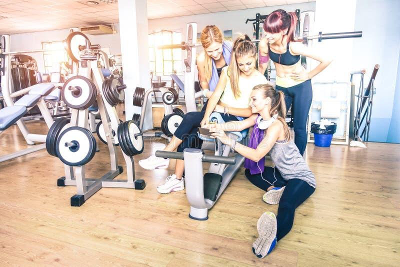 Grupo de mujeres jovenes juguetonas que toman el selfie con el teléfono elegante móvil en el club de fitness del gimnasio - gente foto de archivo