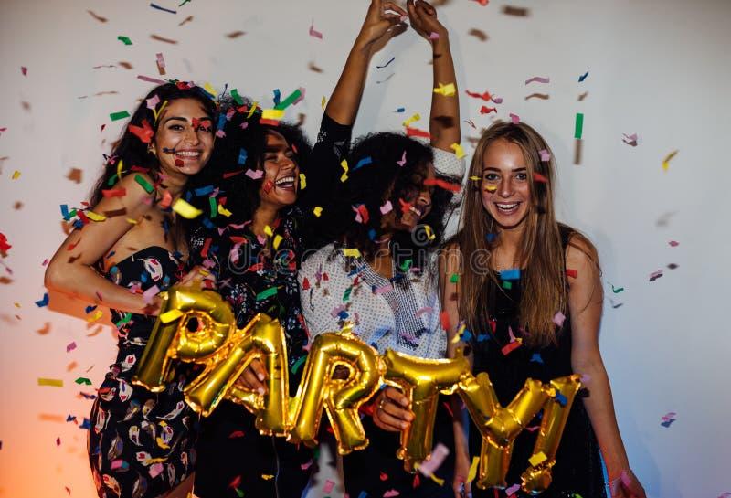Grupo de mujeres jovenes que celebran con confeti foto de archivo libre de regalías