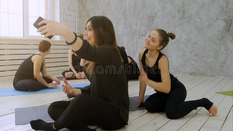 Grupo de mujeres jovenes que hacen el selfie después de entrenamiento en la clase de la yoga imagen de archivo libre de regalías