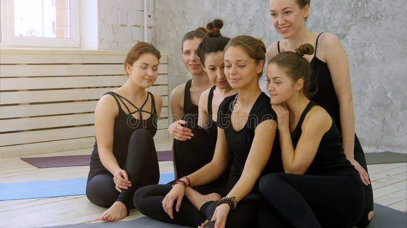 Grupo de mujeres jovenes que toman el selfie usando el teléfono celular en la clase de la yoga foto de archivo libre de regalías