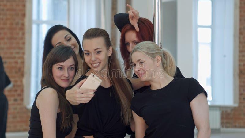 Grupo de mujeres jovenes que toman un selfie durante una rotura en una clase de la aptitud del polo imágenes de archivo libres de regalías