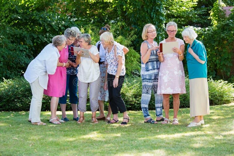 Grupo de mujeres mayores con mucho gusto que miran imágenes y que las discuten, colocándose en el parque después de la lección de foto de archivo libre de regalías