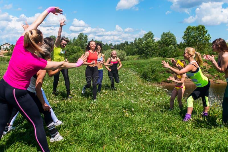 Grupo de mujeres que corren al aire libre divertirse en naturaleza fotografía de archivo