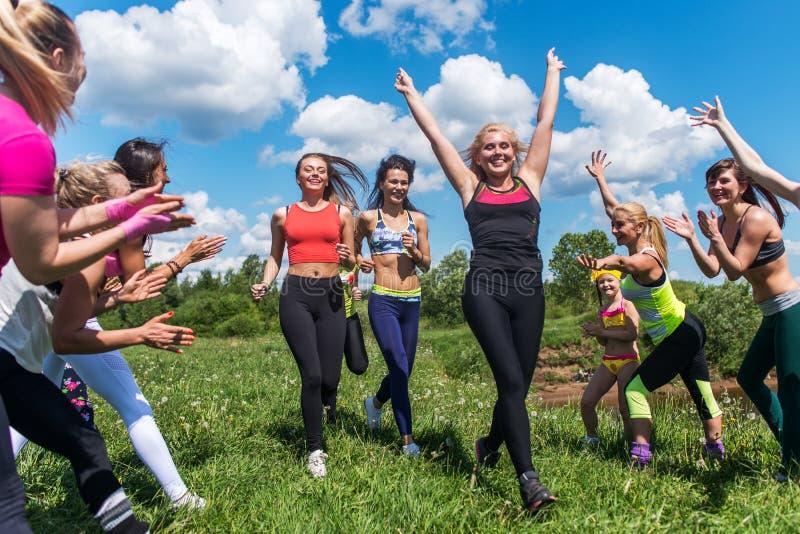 Grupo de mujeres que corren al aire libre divertirse en naturaleza imagenes de archivo