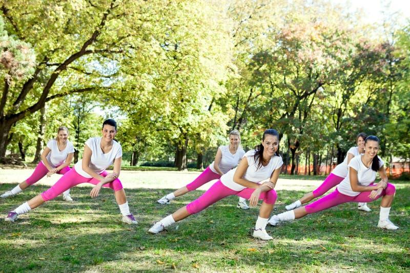 Grupo de mujeres que estiran las piernas foto de archivo