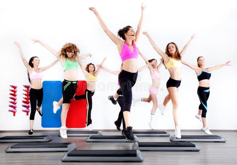 Grupo de mujeres que hacen aeróbicos en de pasos