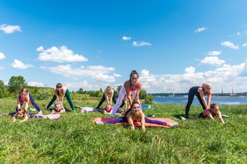 Grupo de mujeres que hacen que estira ejercitando el entrenamiento al aire libre imagen de archivo libre de regalías