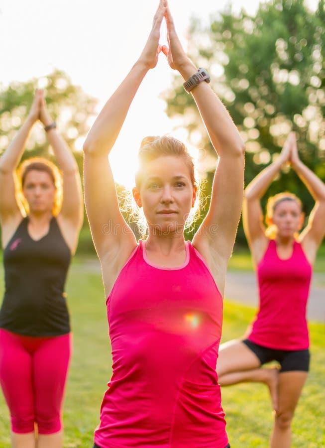 Grupo de 3 mujeres que hacen yoga en la puesta del sol fotos de archivo libres de regalías