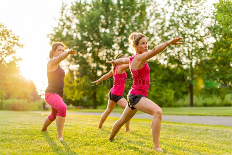 Grupo de 3 mujeres que hacen yoga en naturaleza imagenes de archivo
