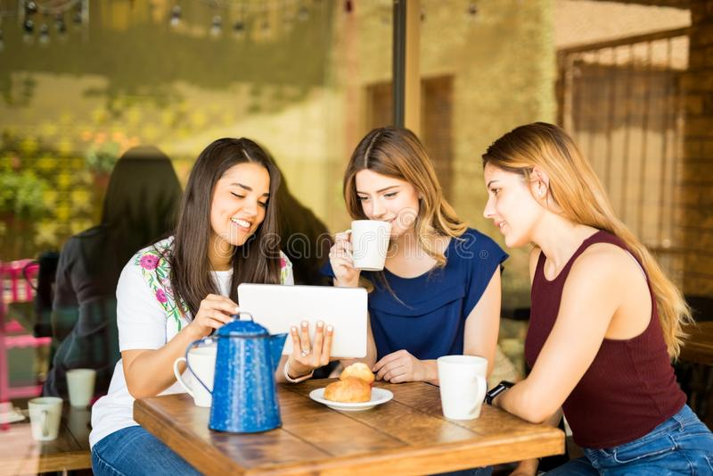 Grupo de mujeres que miran la tableta digital foto de archivo