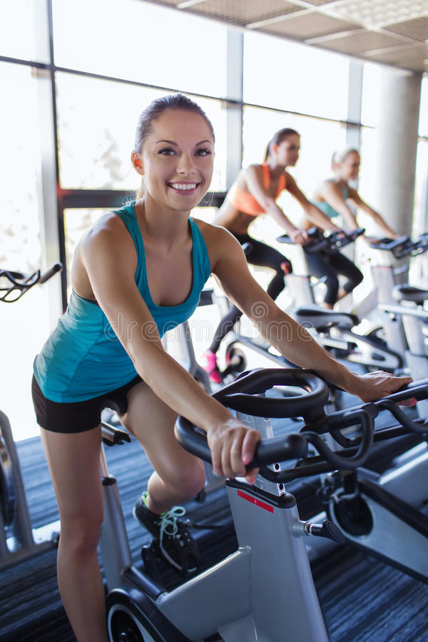 Grupo de mujeres que montan en la bicicleta estática en gimnasio fotos de archivo libres de regalías