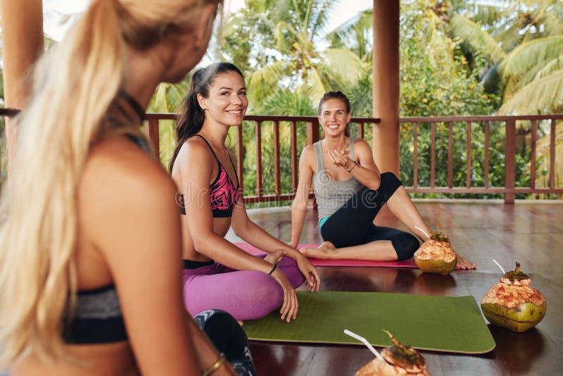 Grupo de mujeres que se relajan después de clase de la yoga imagenes de archivo