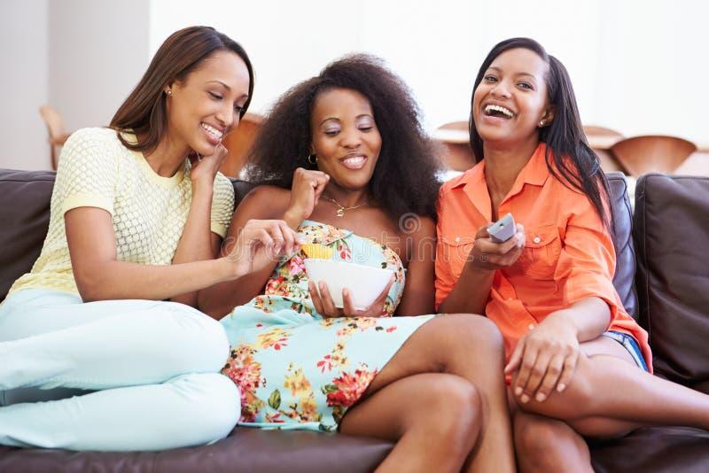 Grupo de mujeres que se sientan en Sofa Watching TV junto fotografía de archivo