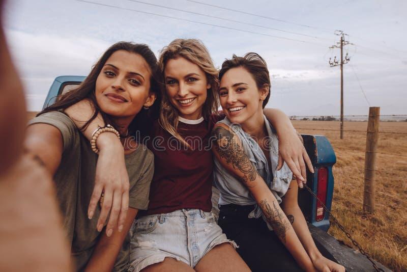 Grupo de mujeres que toman un selfie en la camioneta pickup imágenes de archivo libres de regalías