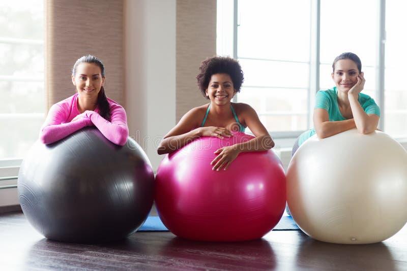 Grupo de mujeres sonrientes con las bolas del ejercicio en gimnasio imagen de archivo