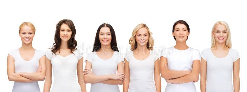 Grupo de mujeres sonrientes en camisetas blancas en blanco fotografía de archivo