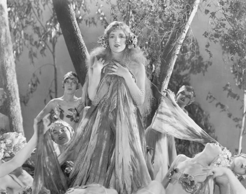 Grupo de mujeres vestidas en la seda y las flores que se colocan en el bosque encantado (todas las personas representadas no son  imagenes de archivo